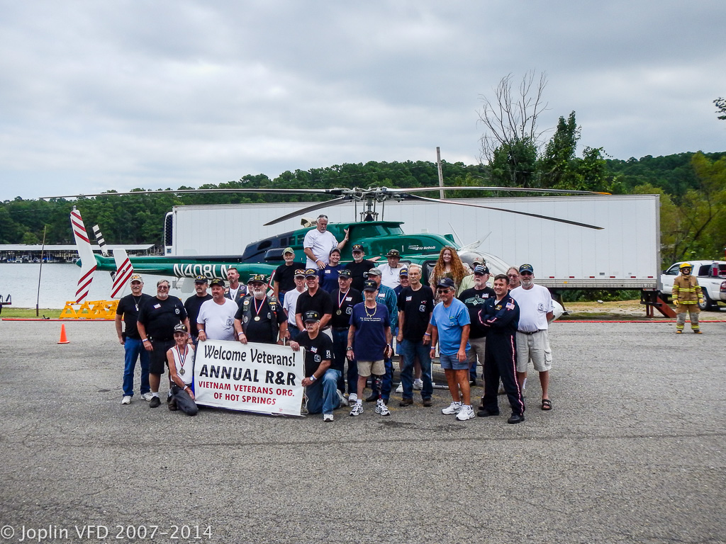 Veterans of the Hot Springs, Arkansas, Vietnam Veterans Organization gather in front of a LifeNet air ambulance during their annual R&R outing at Mountain Harbor Resort.