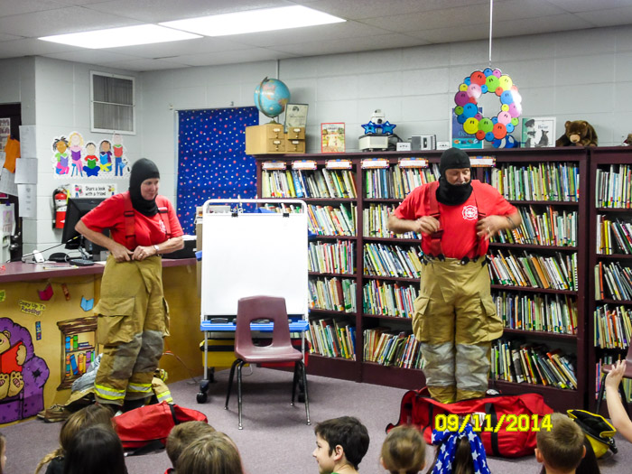 In the schools library, Dan and Bunnie talk to the students about firefighting while they demonstrate how a firefighter dons turnouts.